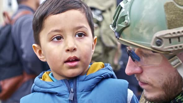 Thumbnail for Little Refugee Child Chatting with Soldier