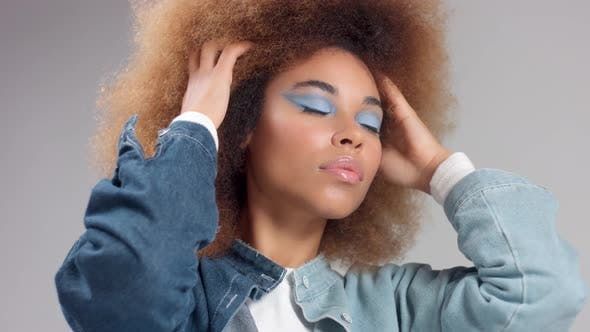 Thumbnail for Mixed Race Black Woman with Big Afro Hair in Denim Style Poses To a Camera
