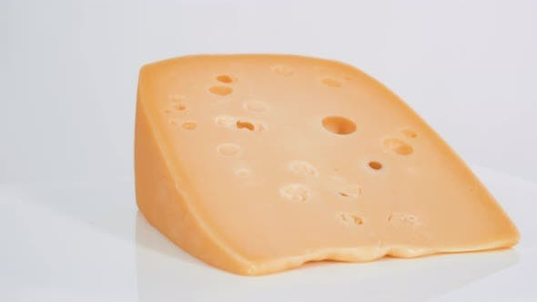 Large slice of semi soft part skim cheese on a white background.