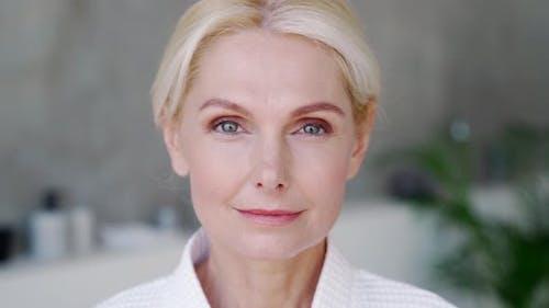 Closeup Portrait of Mid Age Woman Looking at Camera Wearing Bathrobe