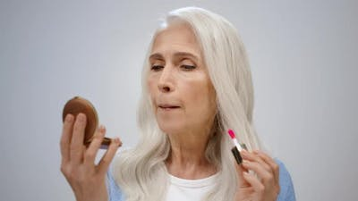 Senior Woman Putting on Makeup in Studio