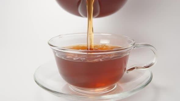 Thumbnail for Mensch gießt einen Tee in einer Tasse aus einer Teekanne