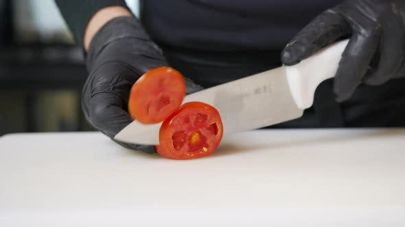 Thumbnail for Chef Takes Cherry Tomatoes Cuts Vegetable Into Halves with Kitchen Knife on Dark Cutting Board