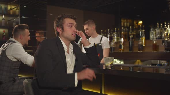 Thumbnail for Man Sits at the Bar and Talks on the Phone