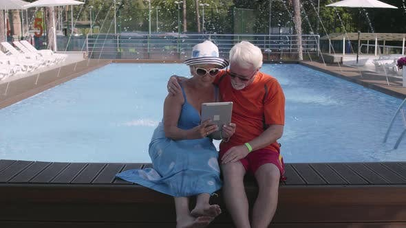 Cover Image for Happy Mature Couple Sitting on the Edge of the Pool with Tablet in Hands