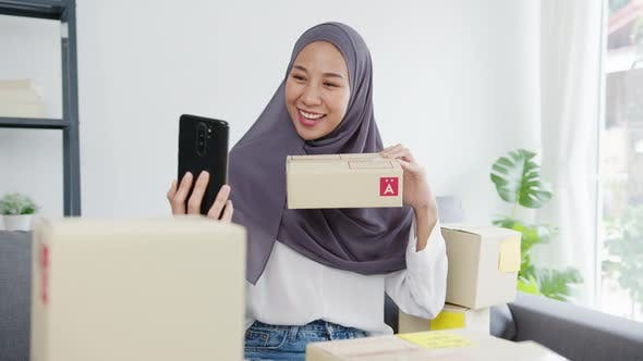 Young Asian muslim woman blogger using mobile phone camera to recording vlog video.