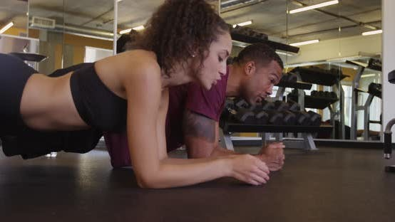 Thumbnail for Fit Hispanic and black couple doing plank core exercises on floor