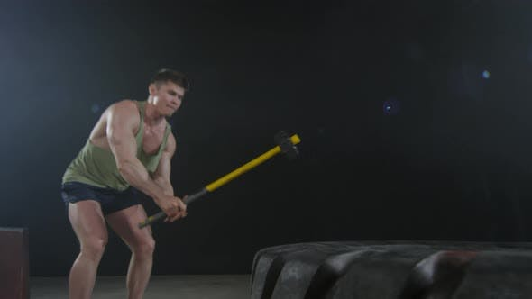 Thumbnail for Man Hitting Tractor Tire with Hammer