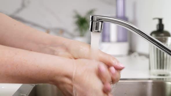 Woman Washing Hands at Kitchen
