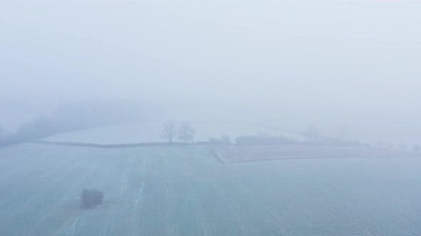 Aerial drone video of countryside and fields in misty foggy weather conditions, rural English scene