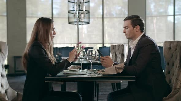 Thumbnail for Business People Using Mobile Phone at Restaurant. Business Couple Working Phones