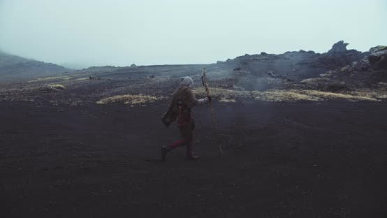 Wandering Hooded Nomad On Black Sand