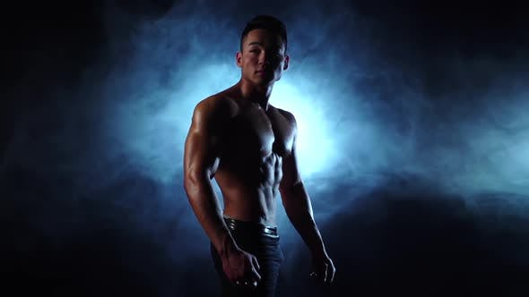Thumbnail for Asian Bodybuilder Man Demonstrates His Body, Strength and Endurance, Black Smoke Background
