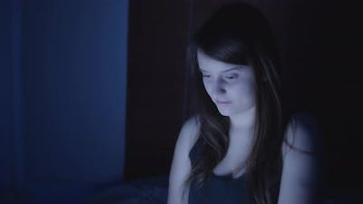 A young woman browsing internet at night