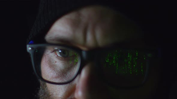 Bearded Hacker in Eyeglasses Working on Computer in the Night Green Programming Code Reflecting on