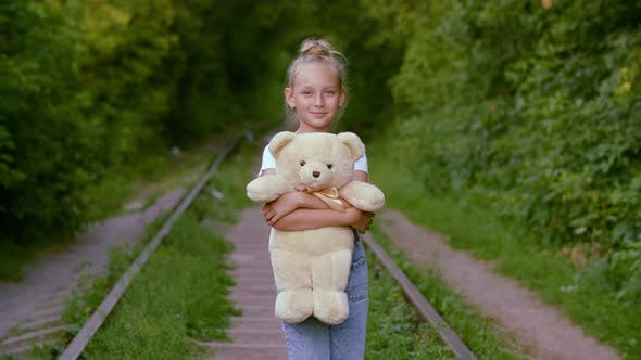 Cover Image for Romantic Girl with Teddy Bear Smiling on Old Railway Background. Happy Teenager Girl Holding White