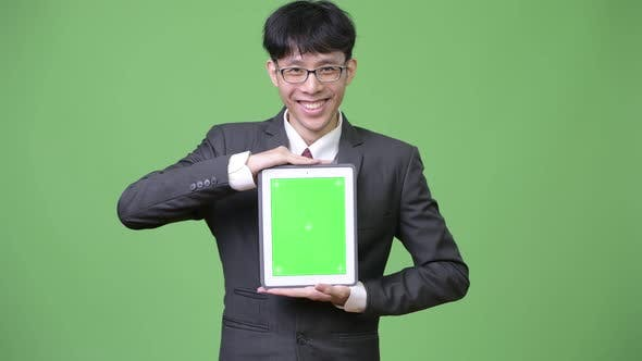 Thumbnail for Young Happy Asian Businessman Showing Digital Tablet To Camera