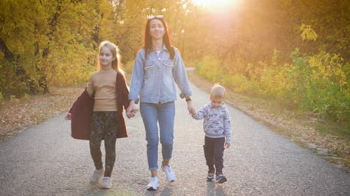 Mother and Two Children Walking in the Park and Enjoying the Beautiful Autumn Nature, Happy Family