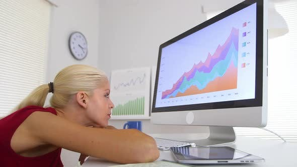 Thumbnail for Business woman reviewing charts on computer