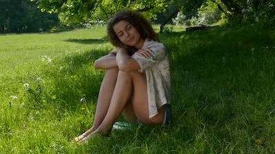 Romantic Girl Sits on the Grass in the Park