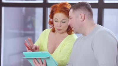 Beautiful Wife Discussing Idea with Husband Scrolling Tablet