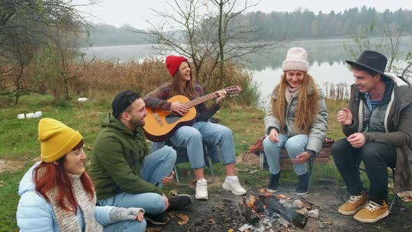 Thumbnail for Happy Friends Sitting Around a Bonfire on the Beach, Playing Guitar and Singing