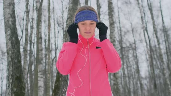Thumbnail for The Female Before the Morning Winter Jog Inserts Headphones in the Ears and Is Preparing To Run