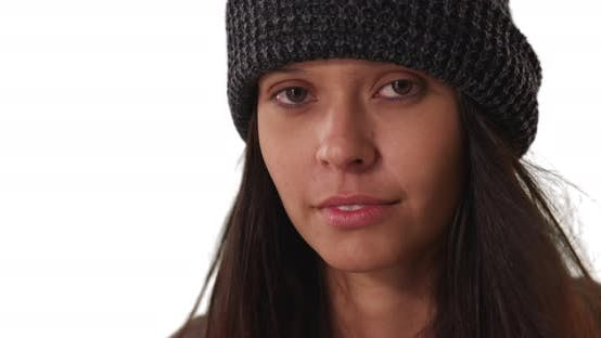 Thumbnail for Close up of woman wearing beanie looking at camera on white background
