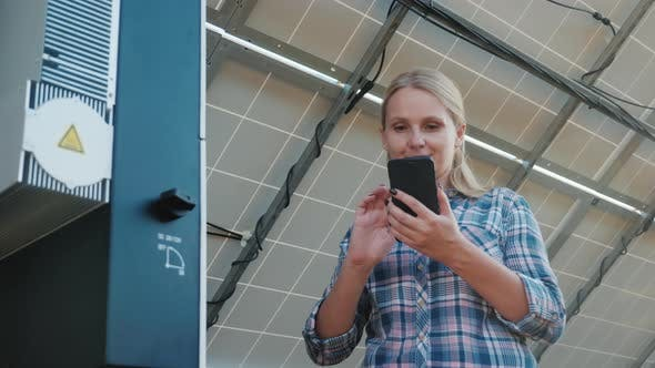 Thumbnail for The Woman Uses a Smartphone, Stands at the Inverter Under the Panels of the House