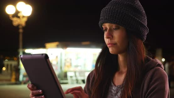 Thumbnail for Millennial caucasian girl using tablet computer on city street at night