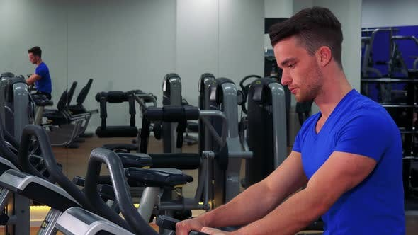 Thumbnail for A Young Fit Man Trains on an Exercise Bike in a Gym - Closeup