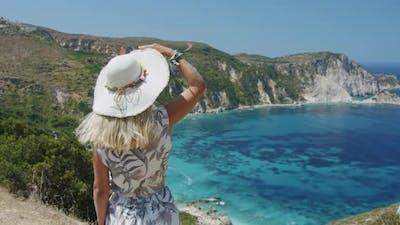 Blond Woman Wearing Sun Hat is Looking at Beautiful Sea Bay Enjoying Scenic Landscape Enjoying