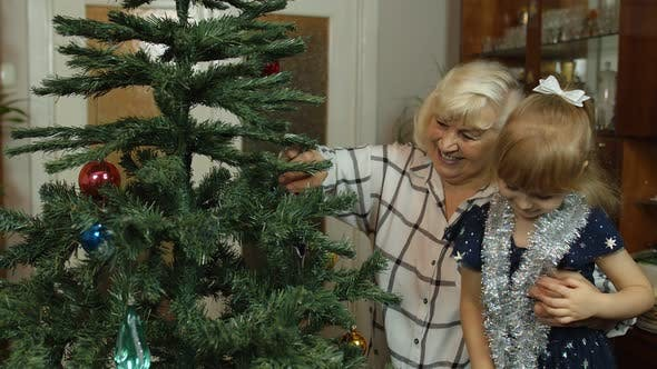 Children Girl with Grandparents Couple Decorating Artificial Christmas Pine Tree at Oldfashion Home