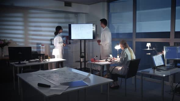 Team of Computer Engineers Discussing Something on a Big TV Screen in Lab