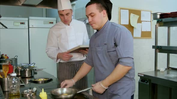 Cover Image for Chef with Cookbook Instructing Cook Trainee How To Fry Shrimps