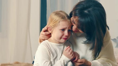 Mom Soothes Her Little Daughter Who Is Crying a Lot