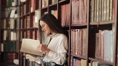 Girl Reading Book Near Bookshelf