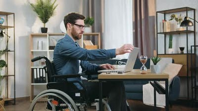 Handicapped Man in Wheelchair Working on Laptop in Home Office at daytime