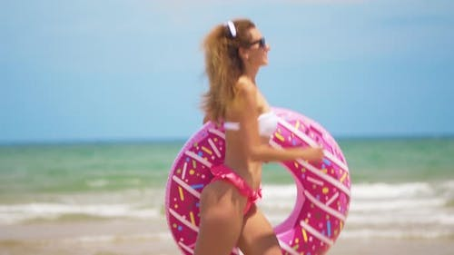 Young Woman Jogging with Inflatable Donut, with Inflatable Ring on the Beach