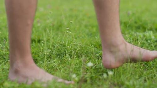 Man Walks Barefoot on Green Grass Camera Movement Closeup
