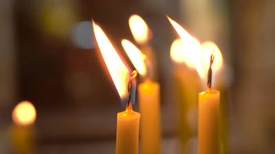 Extreme Close Up Shot of Candles Burning And Flame Waving Inside of Church