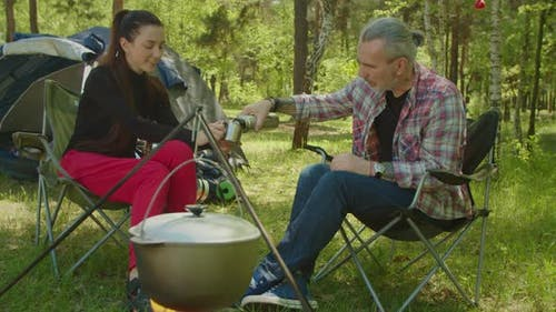 Relaxed Backpackers Pouring Hot Drink Into Travel Mug From Thermos at Campsite