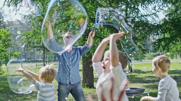 Thumbnail for Group of Little Kids Playing with Soap Bubbles at Performance in Park