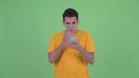 Thumbnail for Happy Young Multi Ethnic Man Using Phone and Looking Surprised