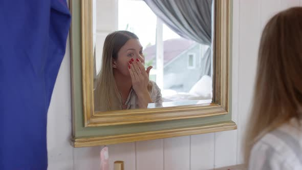 Thumbnail for Woman Putting on Concealer before Mirror