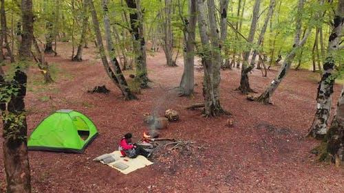 Caucasian Woman Hugs Boy In Camping Spot By Fire