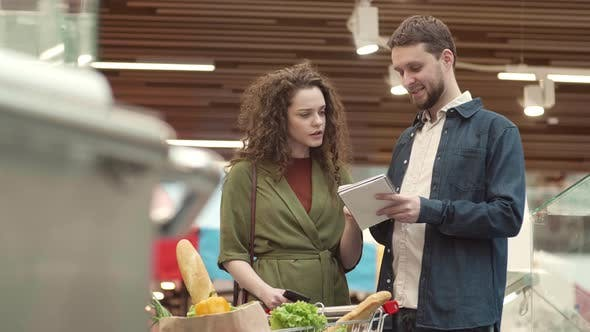 Thumbnail for Young Family Couple Communicating in Grocery Store