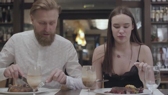 Thumbnail for Portrait of a Young Cute Brunette Woman and Bearded Man Having Supper or Dinner in a Restaurant or
