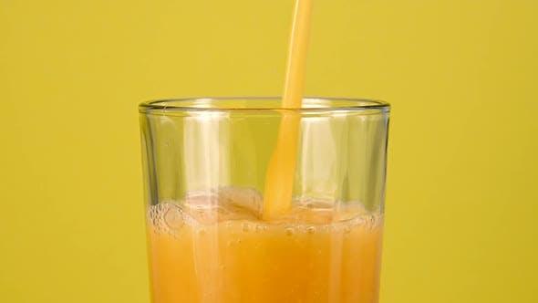 Verser le jus d'orange dans le verre sur jaune