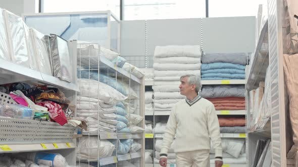 Thumbnail for Elderly Man Walking in Home Department Store, Shopping for Bedding